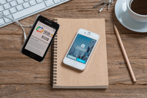 Imagem ilustrativa de smartphones sob mesa com aplicativos referentes a gestão de carreira em uso