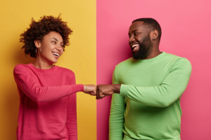 positive-dark-skinned-young-woman-and-man-bump-fists-agree-to-be-one-team-look-happily-at-each-other-celebrates-completed-task-wear-pink-and-green-clothes-pose-indoor-have-successful-deal